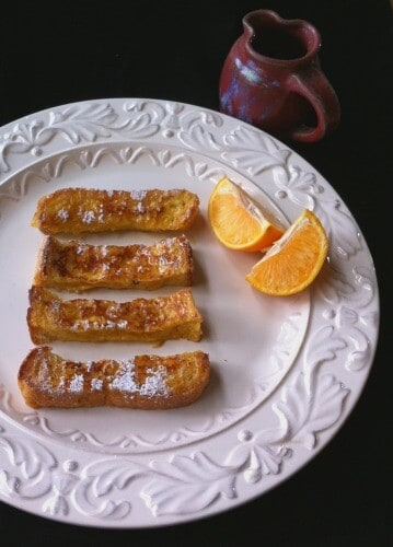 french toast slices on plate with orange quarters