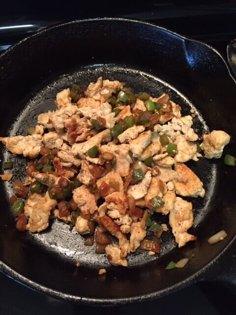 Browned sliced chicken mixed with peppers and onions