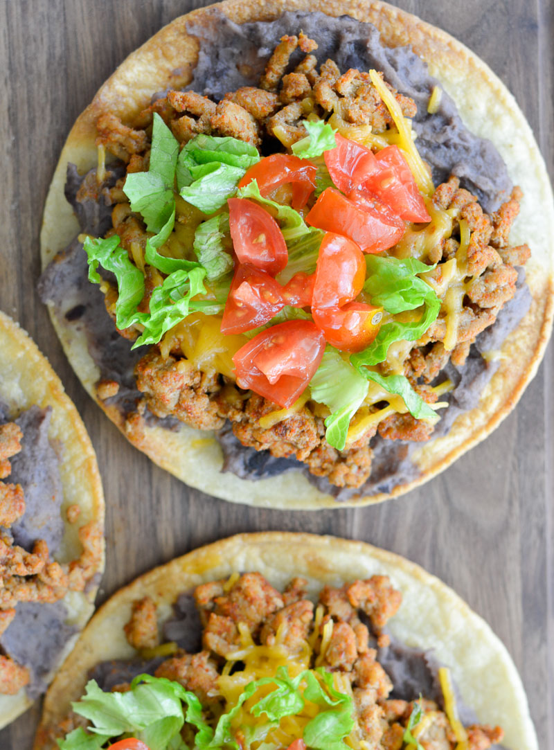 These quick and easy tostadas are ultra crispy and loaded with refried beans, taco meat, cheese and a zesty sauce!