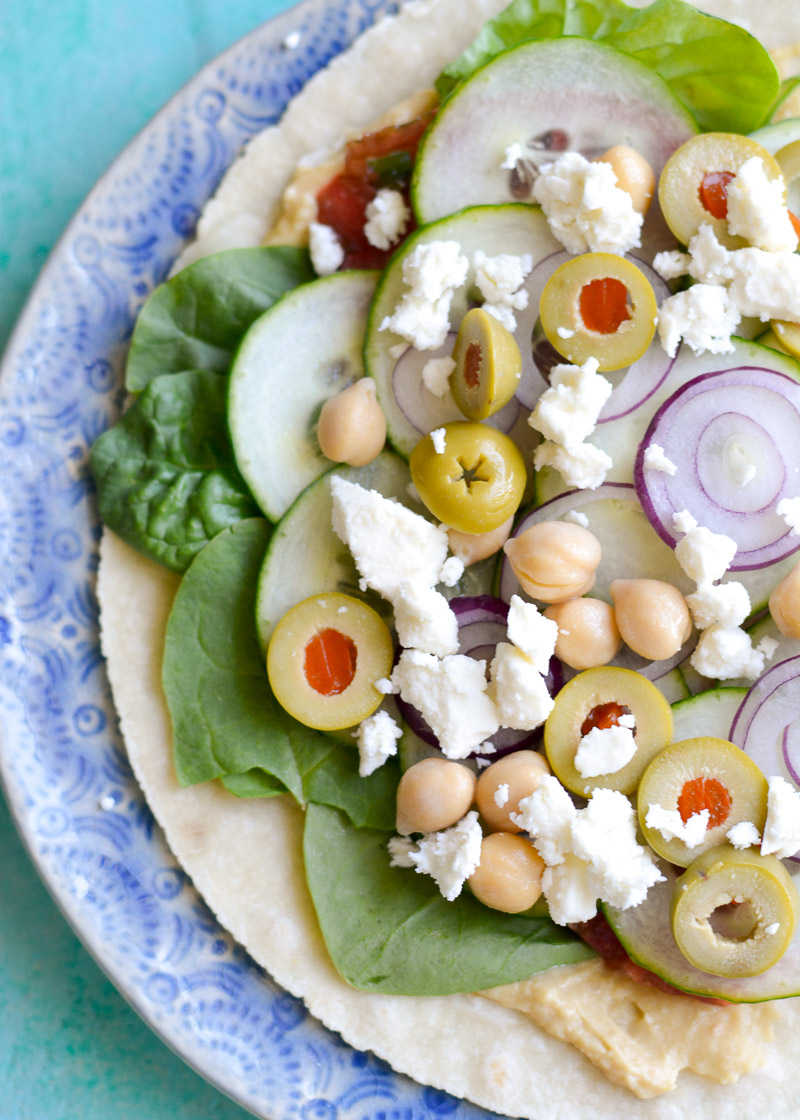 This easy Hummus Veggie Wrap is a healthy dish that requires no cooking! Loaded with fresh vegetables, creamy hummus, tangy feta, and protein rich chick-peas this is a vegetarian meal you will love!