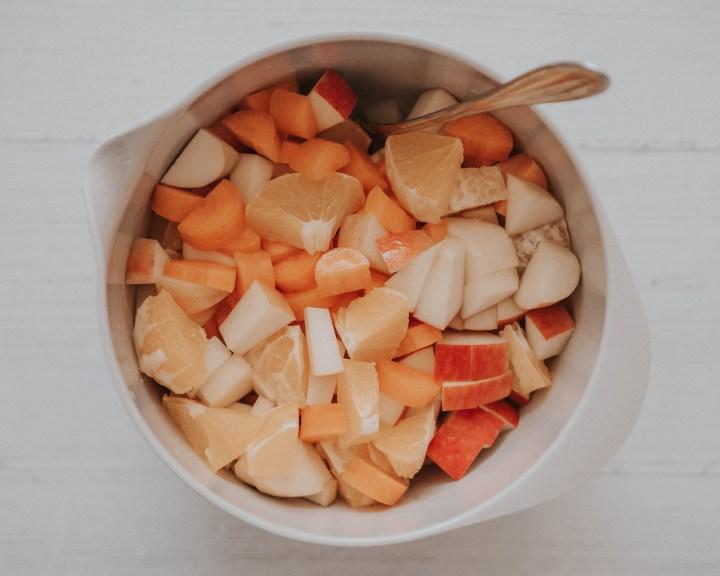 Vorbereitung vom Frühstückssaft: Schüssel mit geschnittenen Zutaten: Orange, Apfel und Möhre
