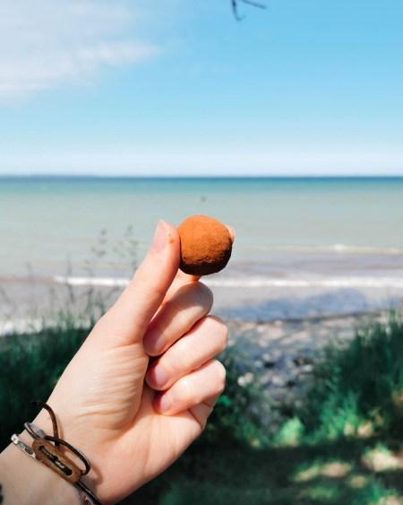 Marzipan Energy Ball mit Kakaopulver ummantelt in der Hand, im Hintergrund ist das Meer zu sehen