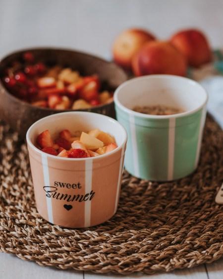 Haferflocken mit Obst (Erdbeeren, Pfirsiche und Aprikosen) als Topping in bunten Eisbechern, eine Schale Obst im Hintergrund