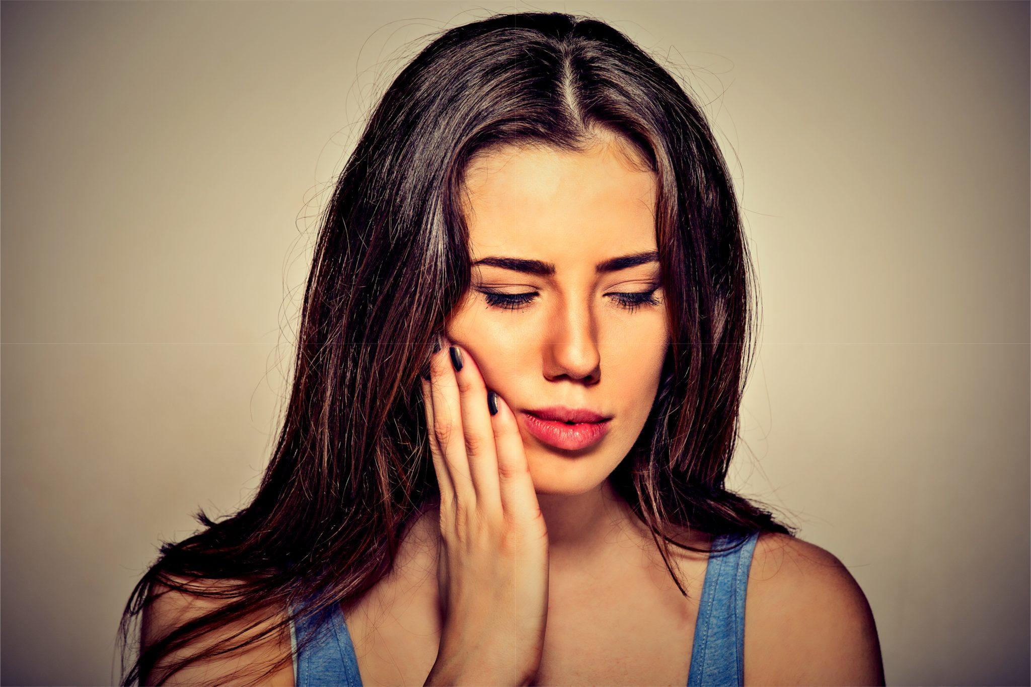 口内炎で頬を押さえている女性