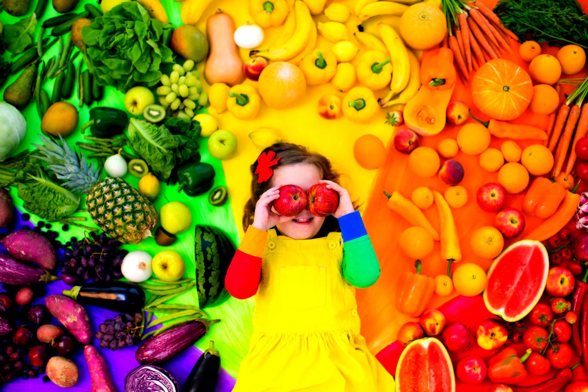 カラフルな野菜と果物に囲まれた子ども