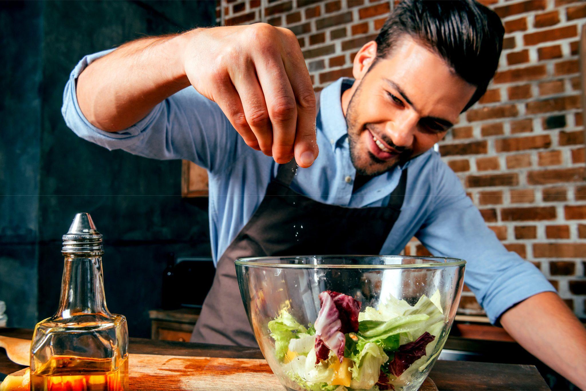 料理に塩をふってる男性
