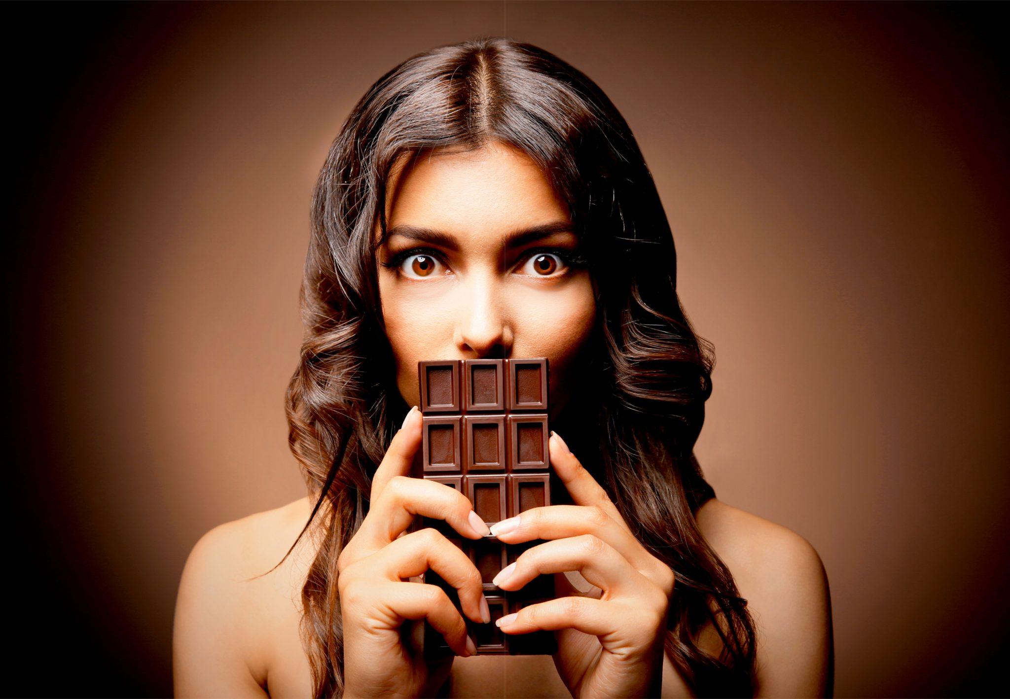 チョコレートを口元で持っている女性