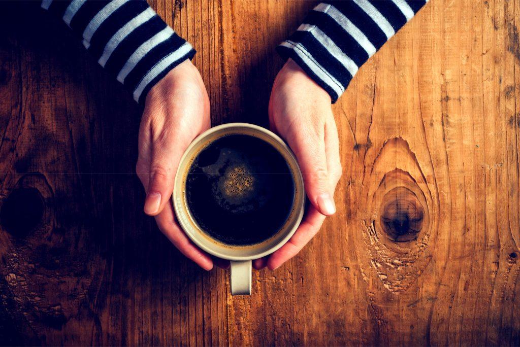 コーヒーを両手で持っている女性