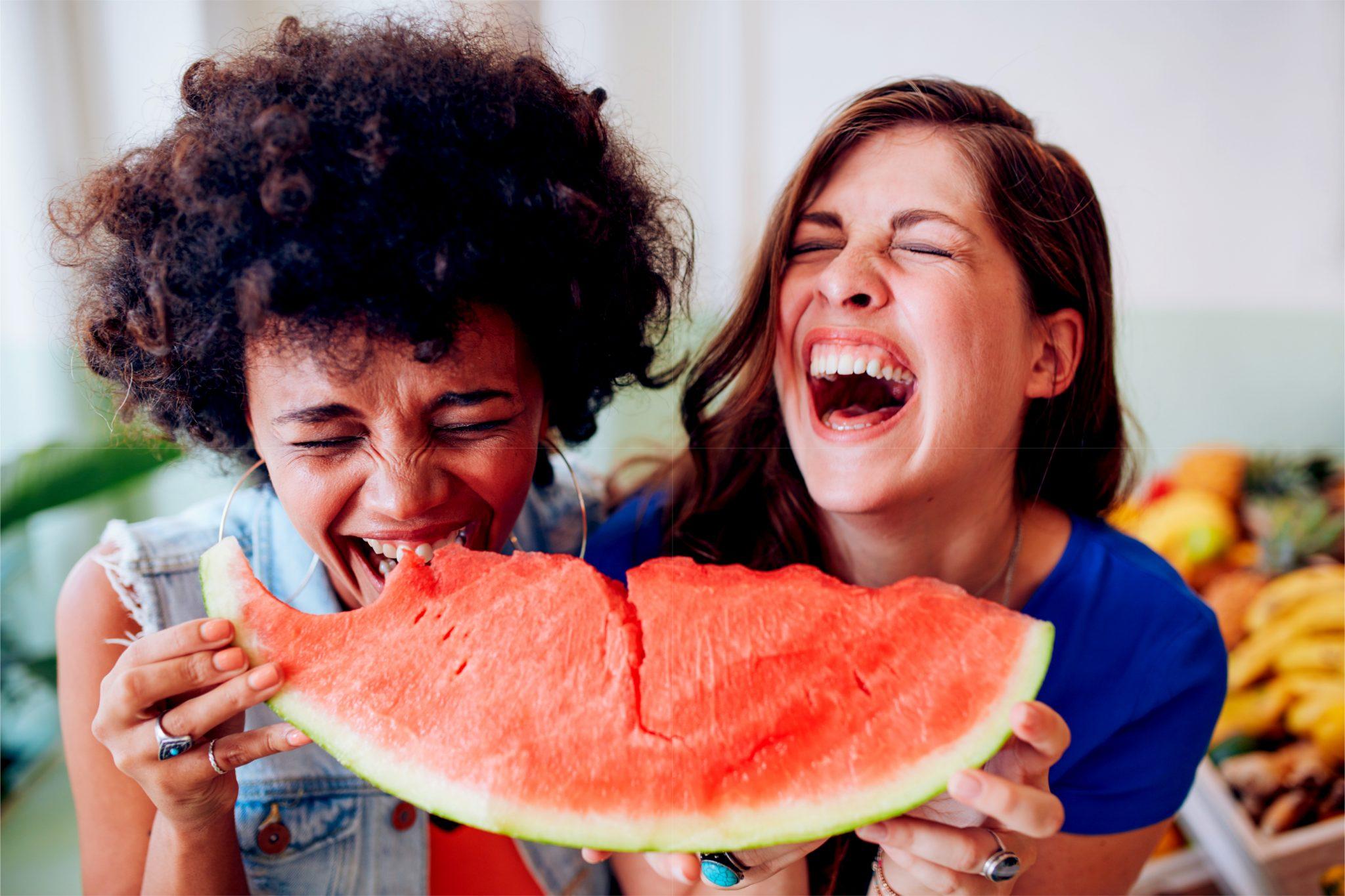 大きスイカを女性二人が一緒に食べている
