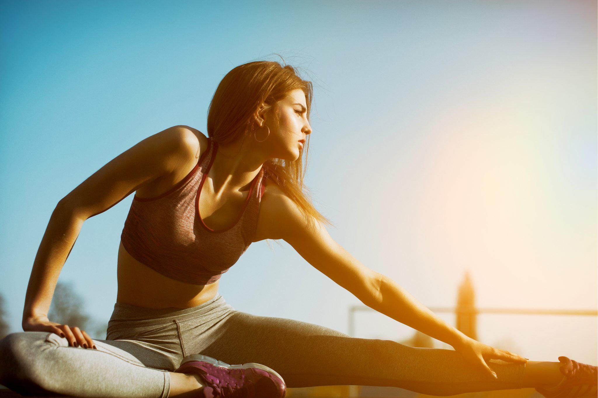 運動後のストレッチで足を延ばしている女性