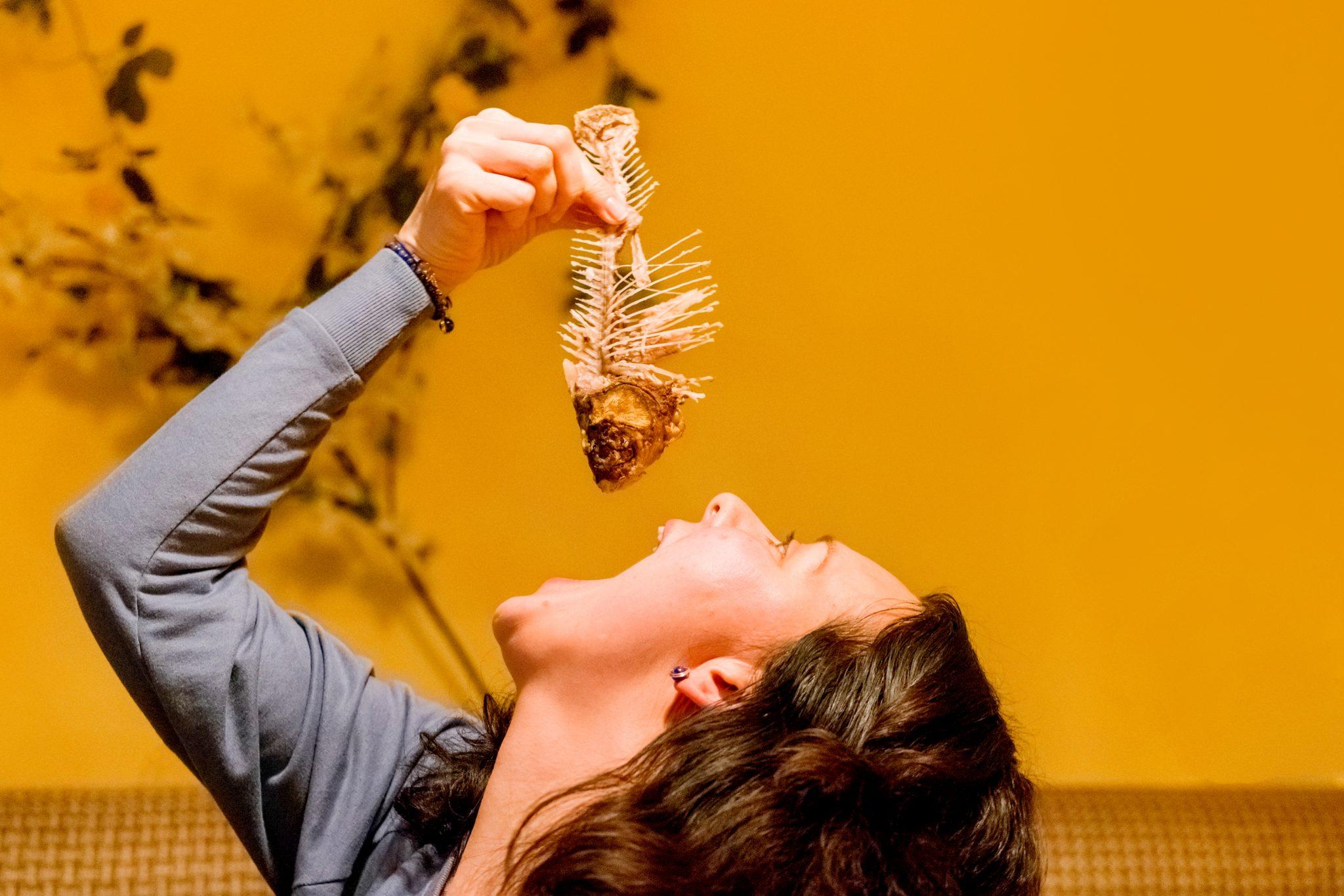 魚の骨を丸ごと食べようとしている女性