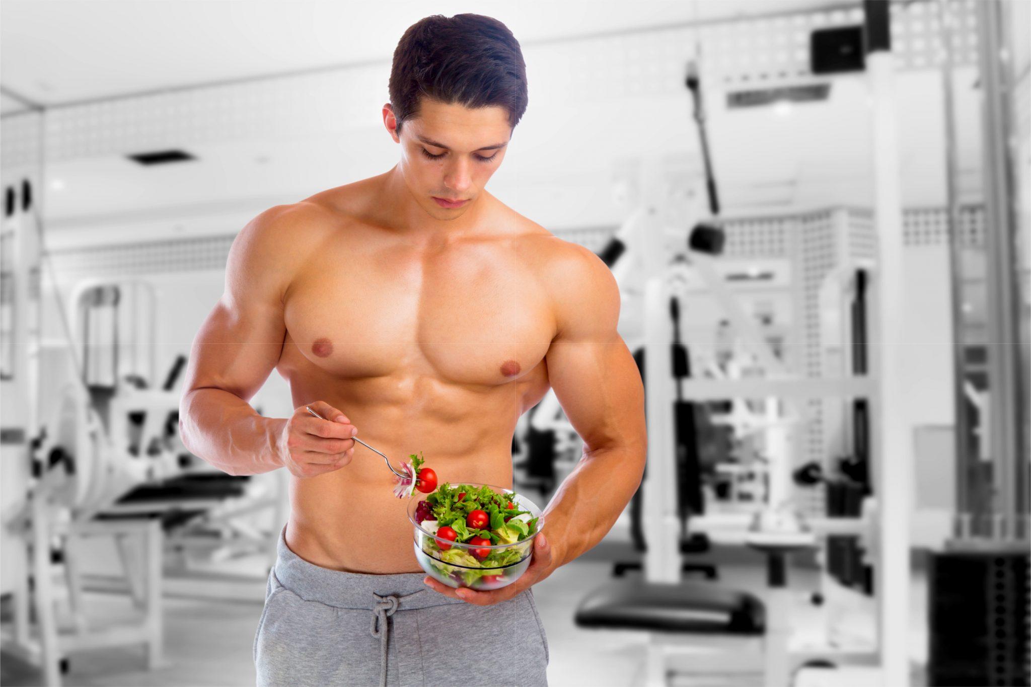 ジムで筋トレ後にサラダを食べているマッチョな男性