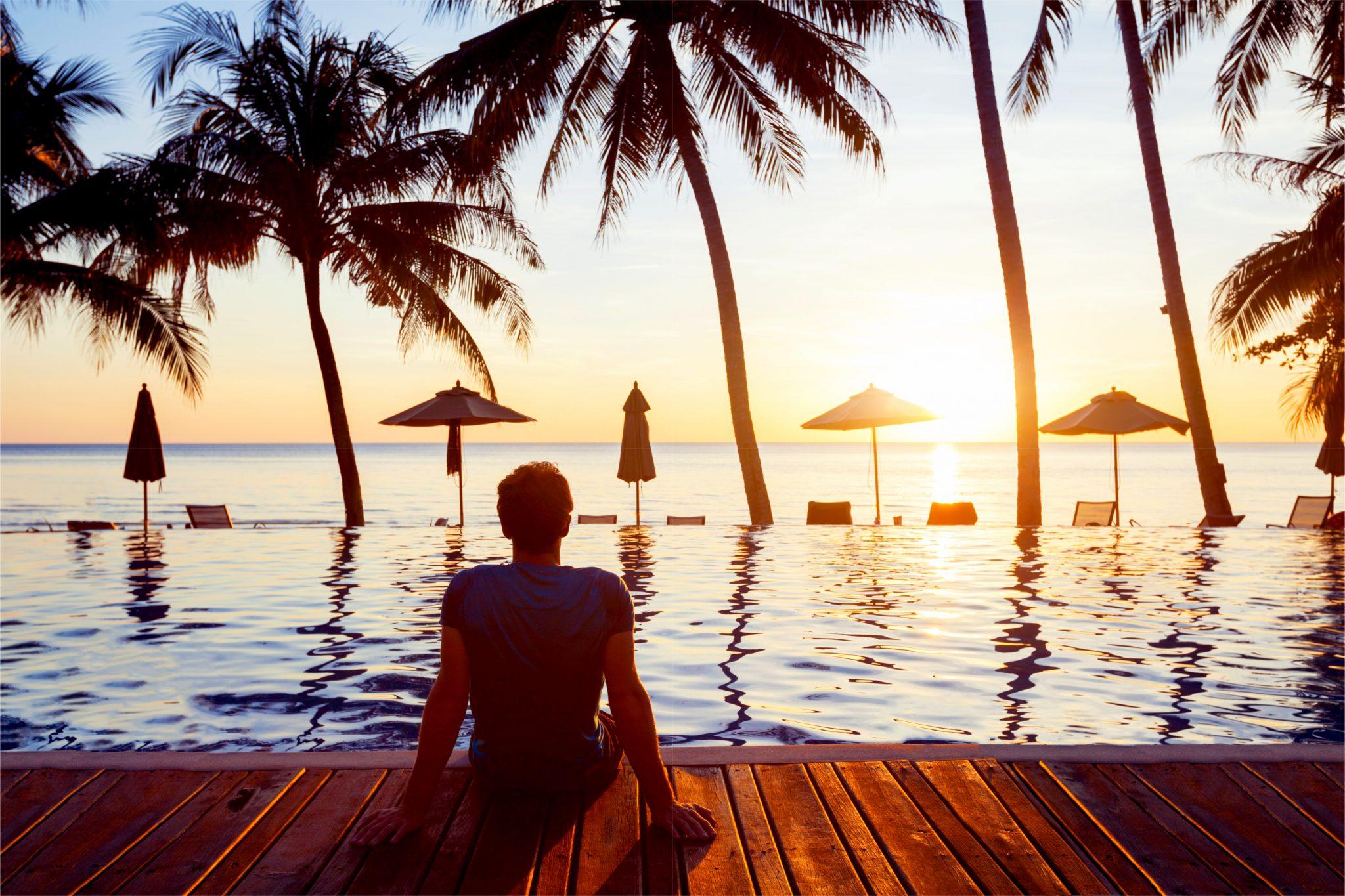 海辺で夕日を見ながらリラックスしている男性