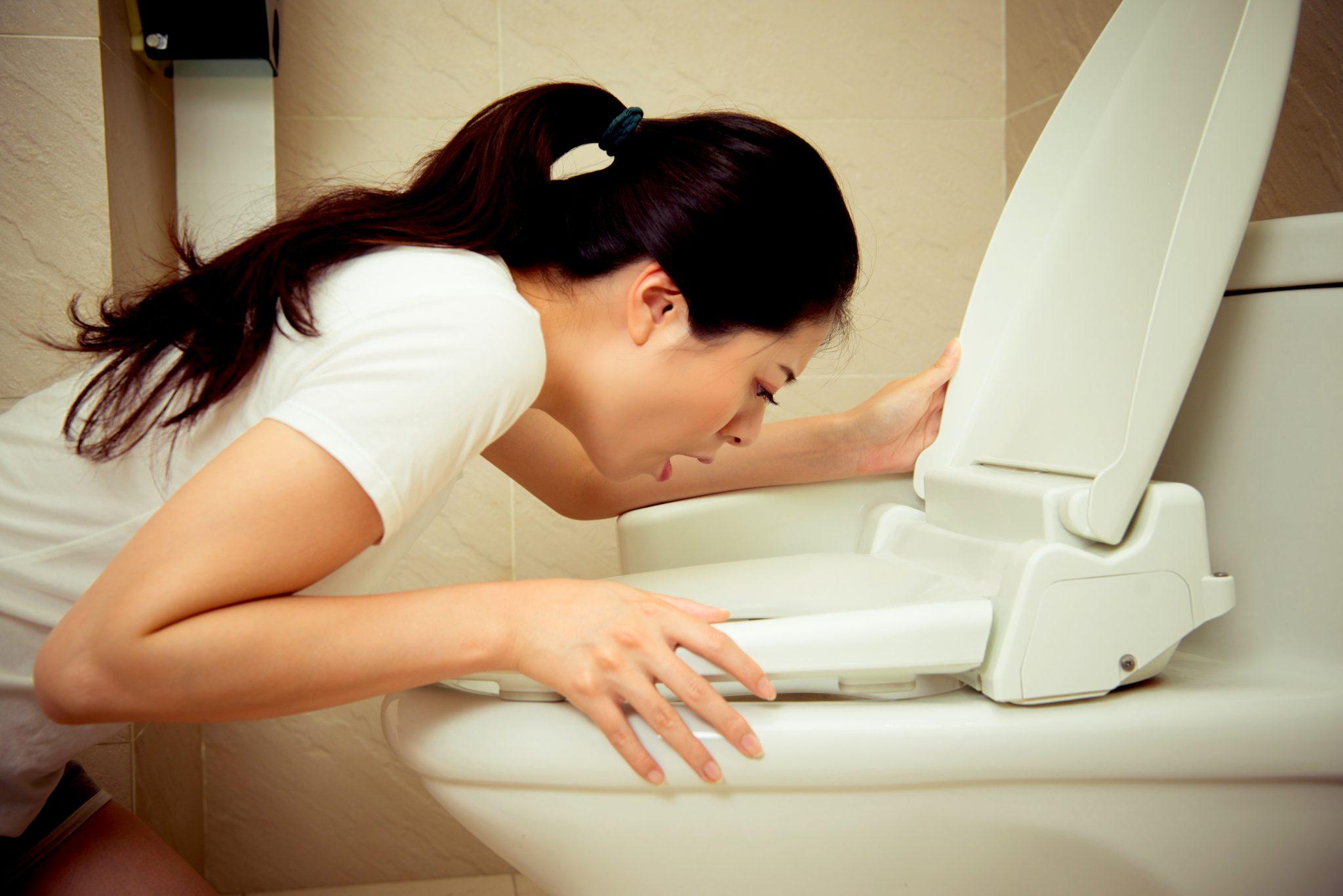 トイレで吐いている女性