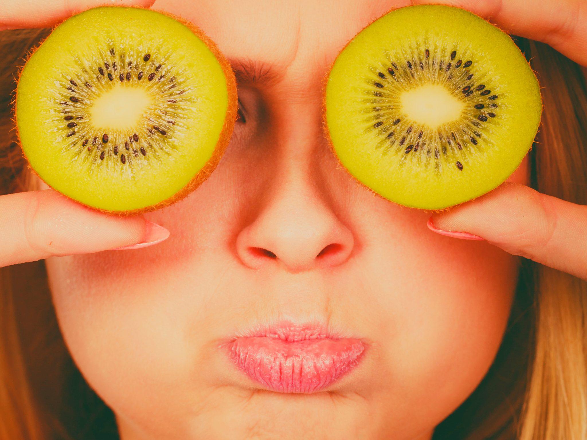 キウイフルーツを目にして写真を撮ってる女性
