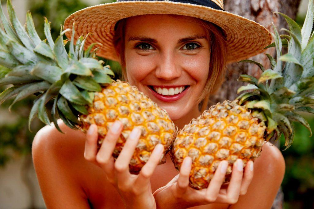 パイナップルを両手に持って写真を撮った女性