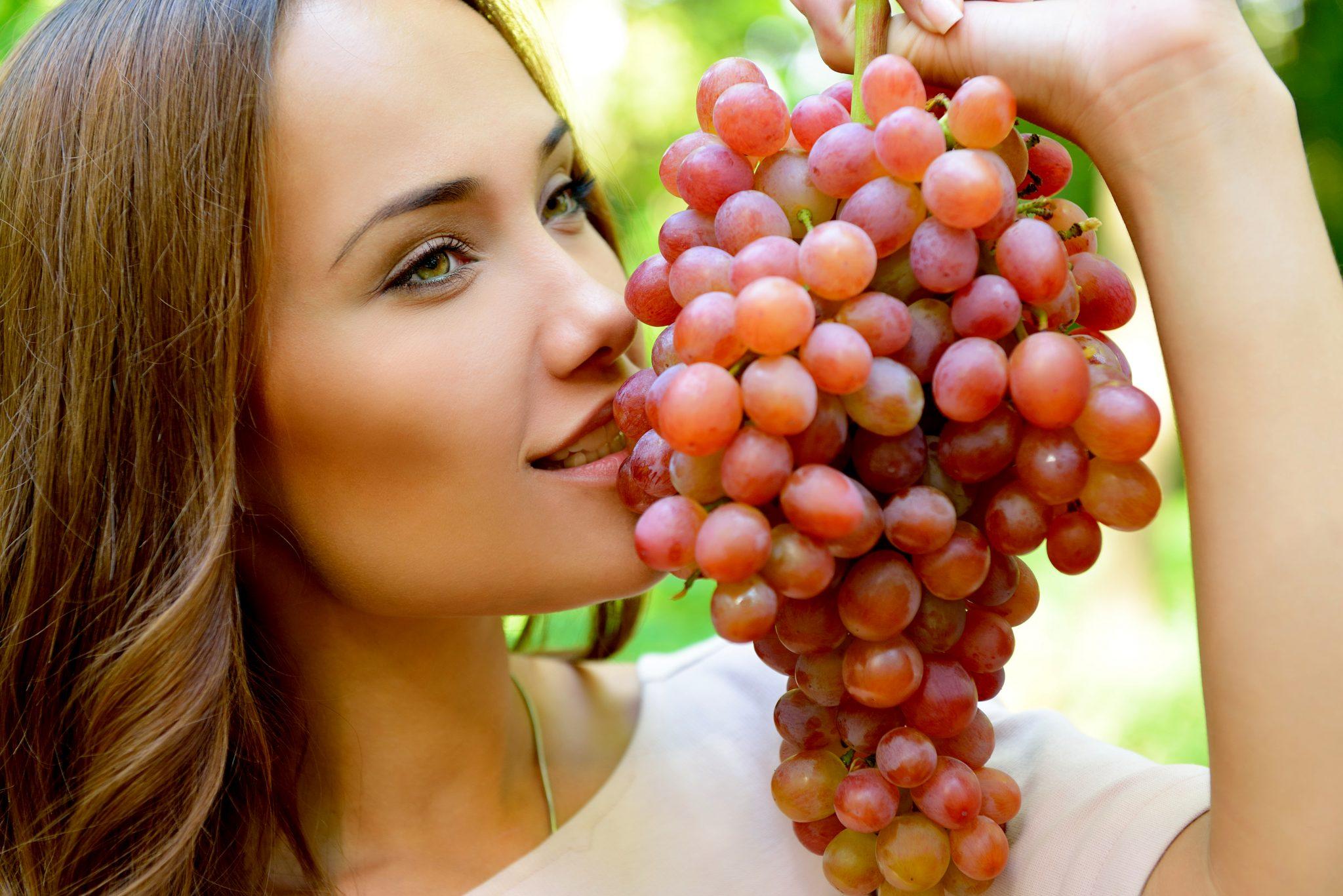 綺麗な女性がブドウを食べている