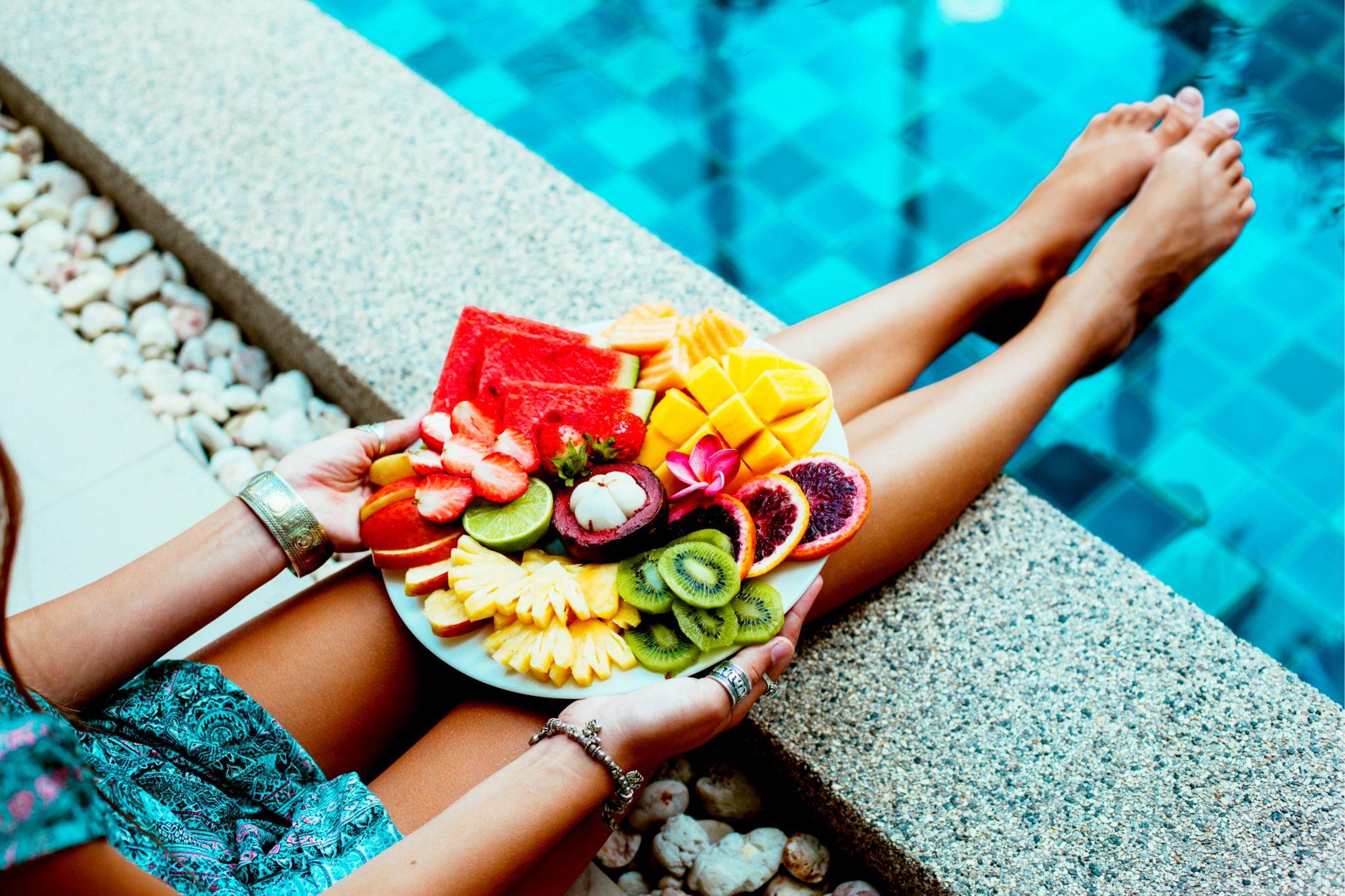 綺麗な女性がプールサイドでフルーツを食べている