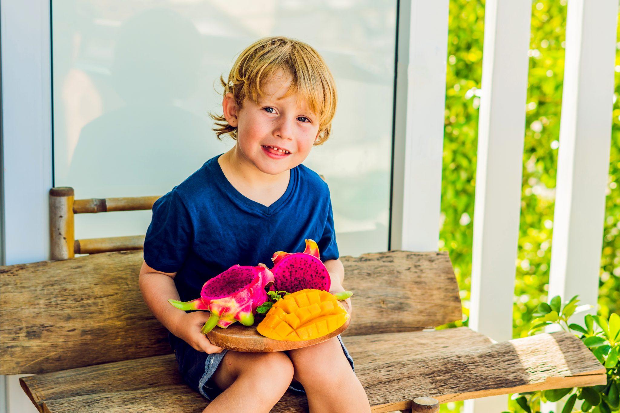 ドラゴンフルーツとマンゴーを持っている男の子