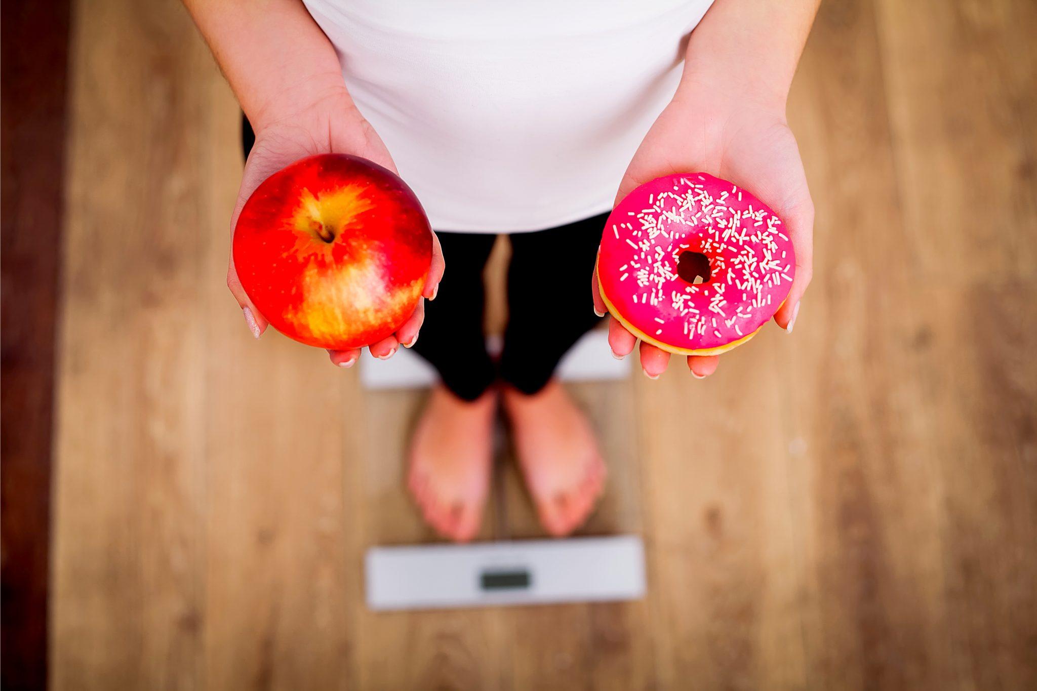 リンゴとドーナツを持って体重計に乗っている女性