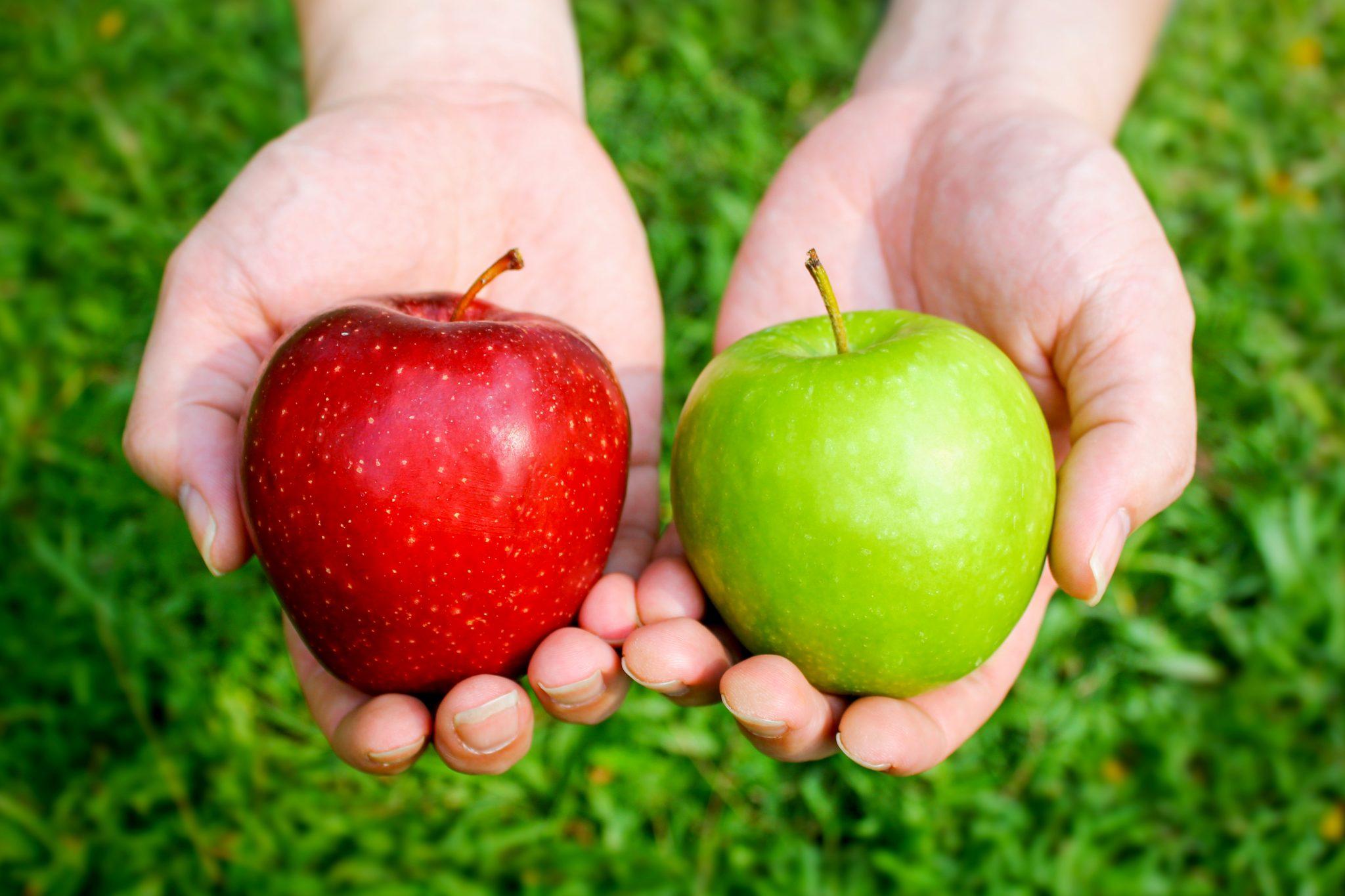 赤いリンゴと青りんごを持っている人