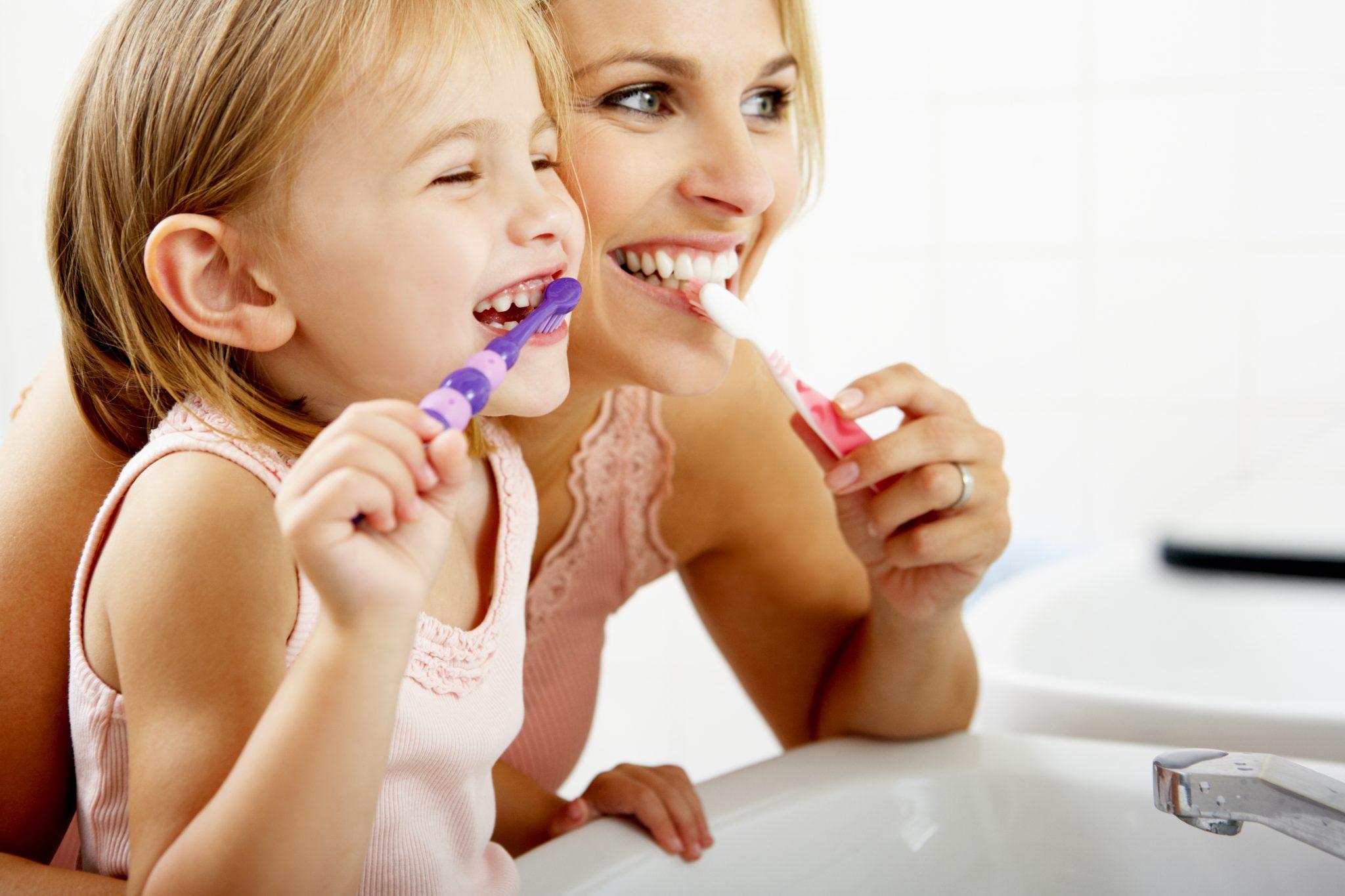 お母さんと娘が一緒に歯磨きをしている