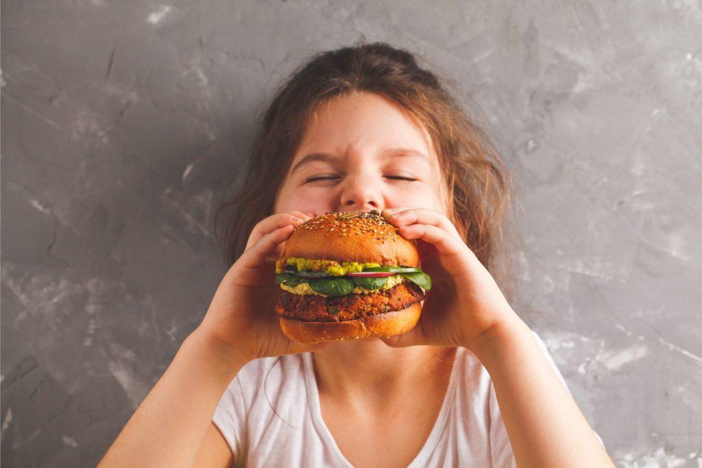 ハンバーガーにかぶりついている子ども