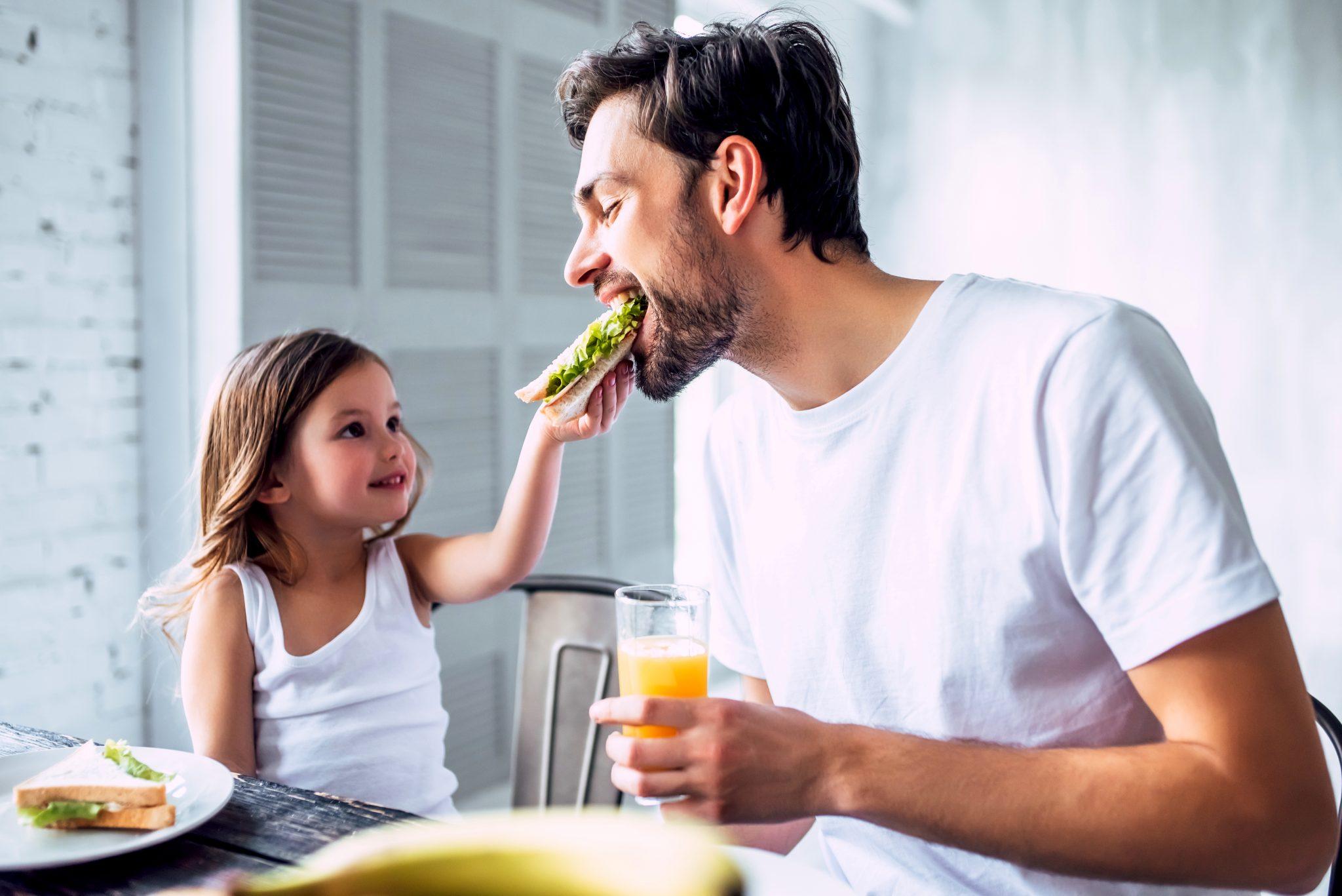 朝食で娘がパパにホットサンドを食べさせてあげている
