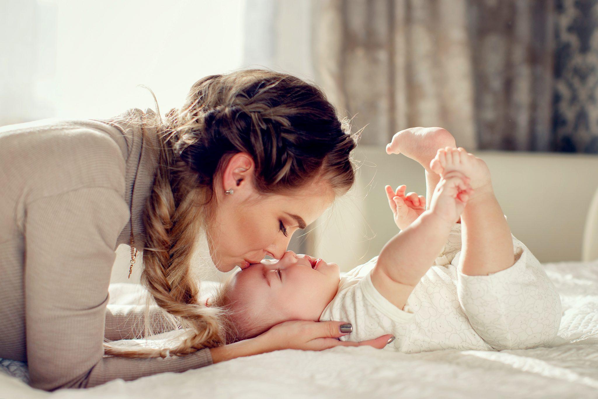 お母さんが赤ちゃんの額にキスをしている