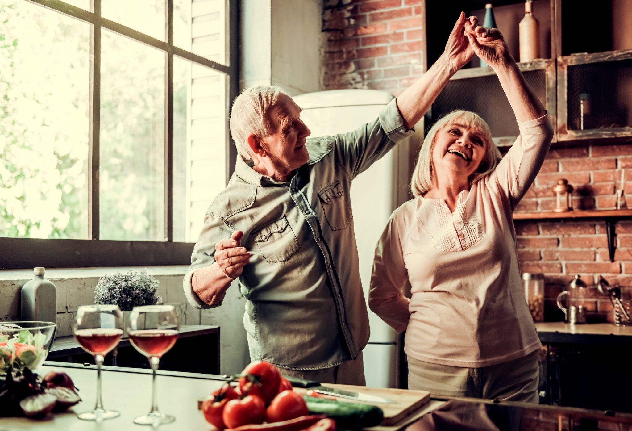 料理しながらダンスしている健康な老夫婦