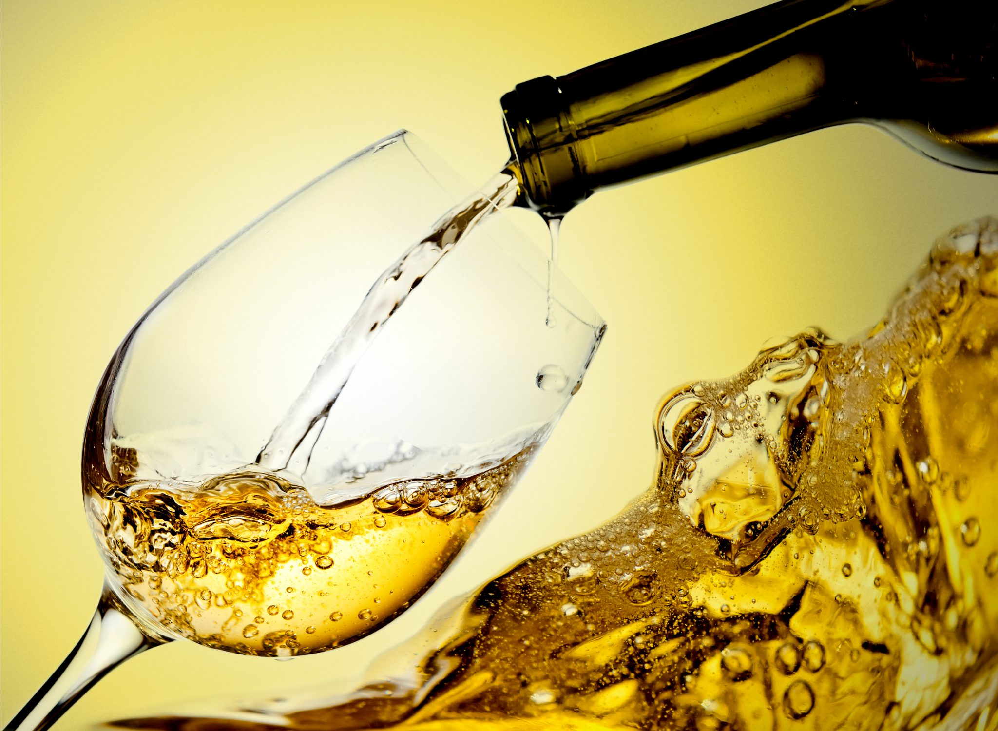 ワイングラスに白ワインを注いでいる