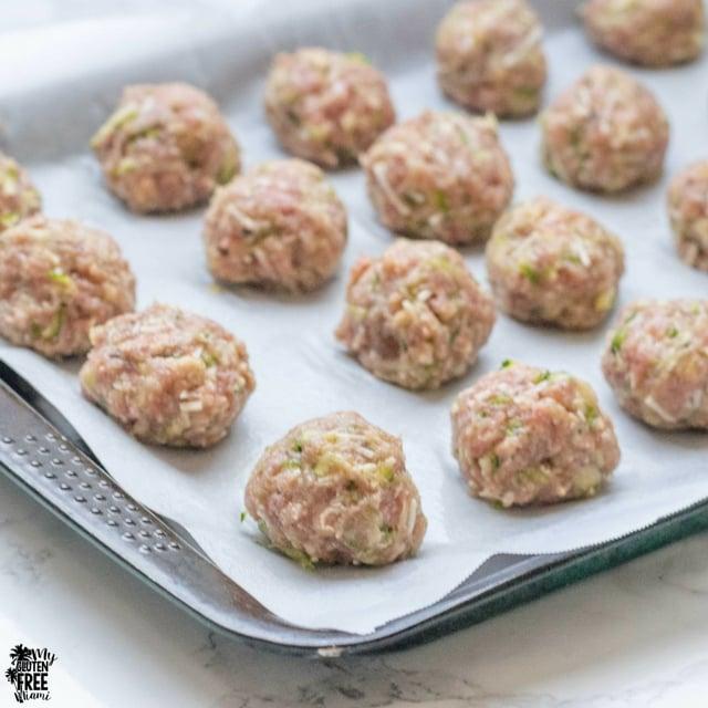 Raw gluten free turkey zucchini meatballs on baking sheet