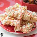 Plate of gluten free marshmallow popcorn bars with red icing and heart sprinkles.