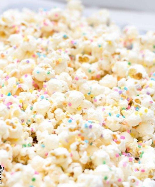 white chocolate popcorn drying on a sheet pan