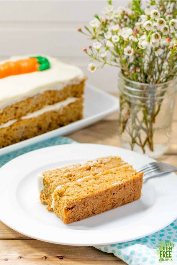 Slice of easy to make gluten free carrot cake on table with flowers