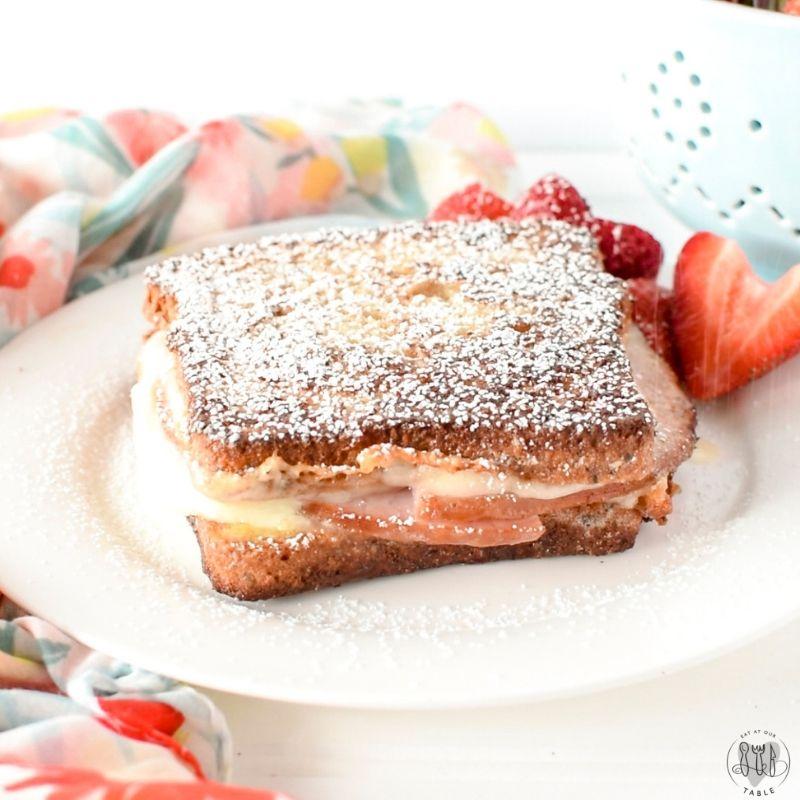 gluten free monte cristo sandwich on a plate sprinkled with powdered sugar