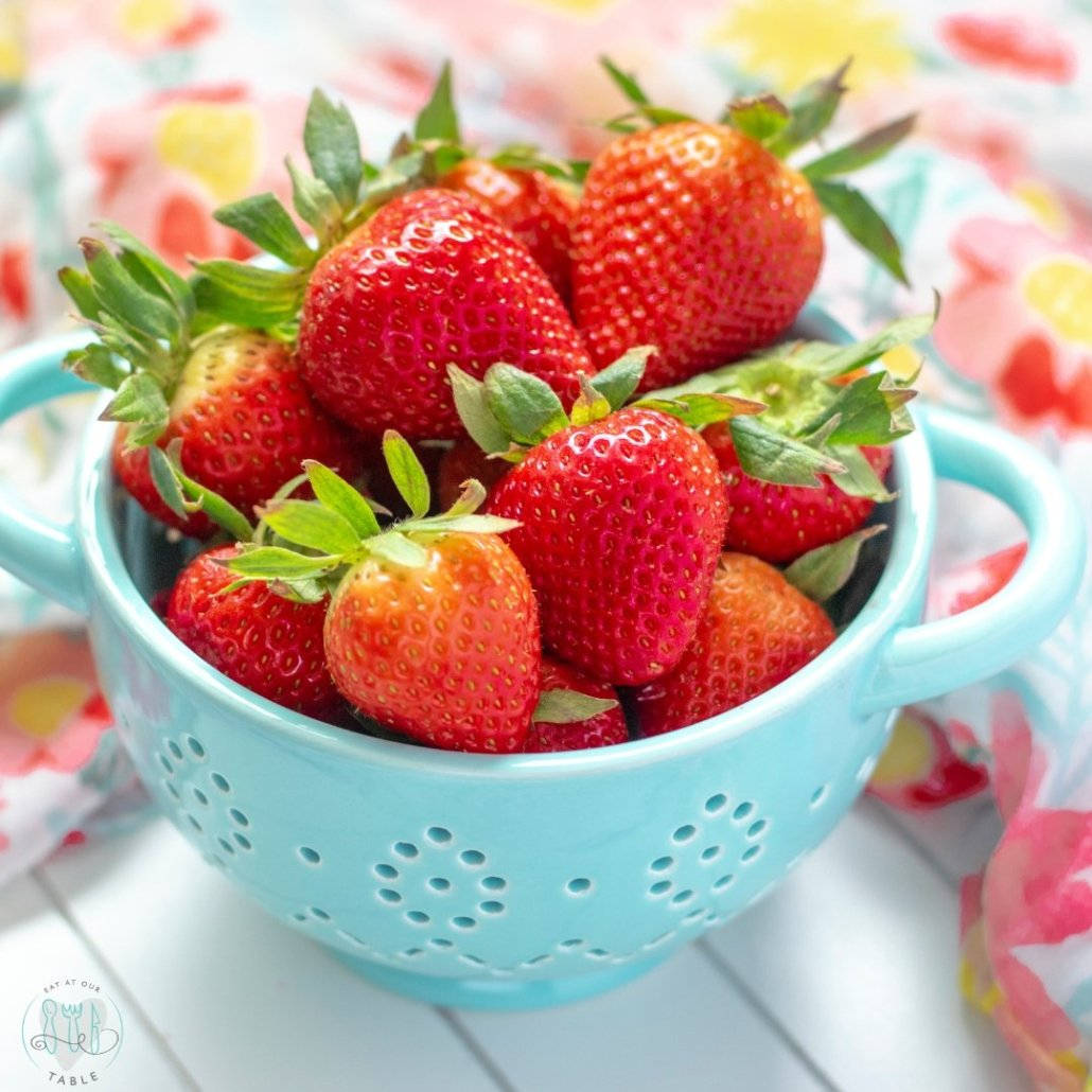 Fresh strawberries in a small blue colander with a flowered scarf