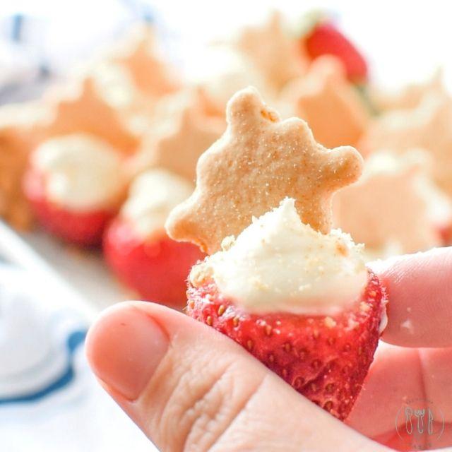 hand holding cheesecake stuffed strawberries