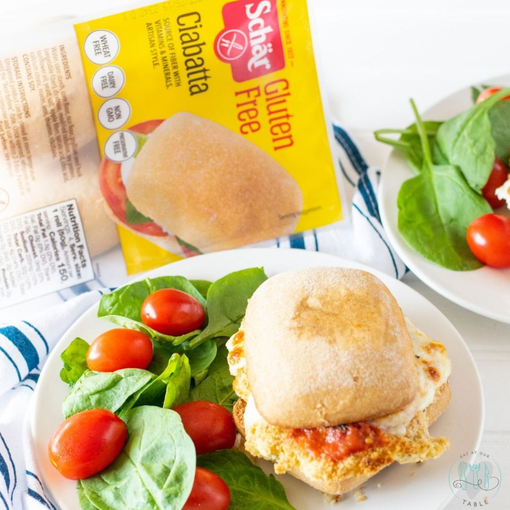 gluten free chicken parmesan sandwich on a plate with salad
