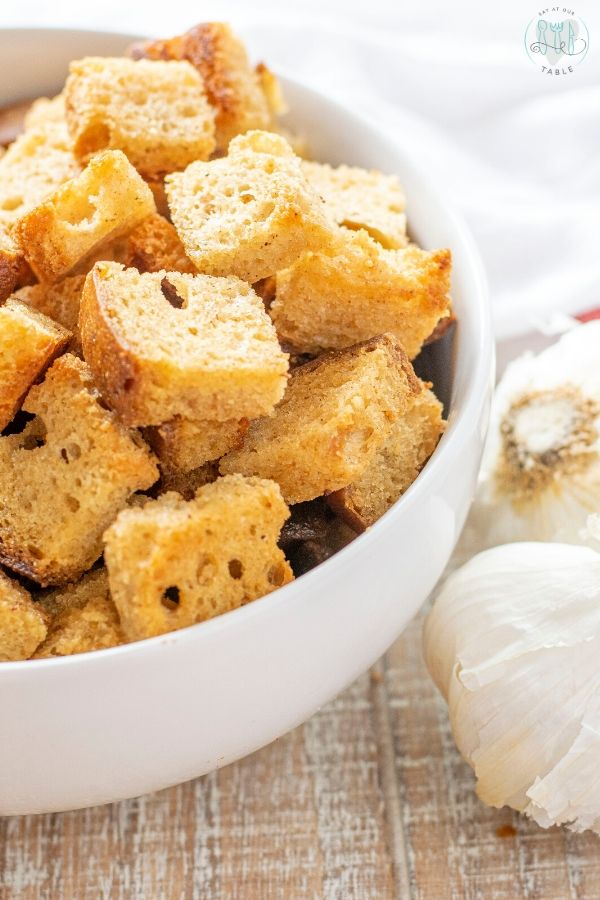 bowl of oven baked garlic and butter croutons with garlic bulbs made from gluten free bread