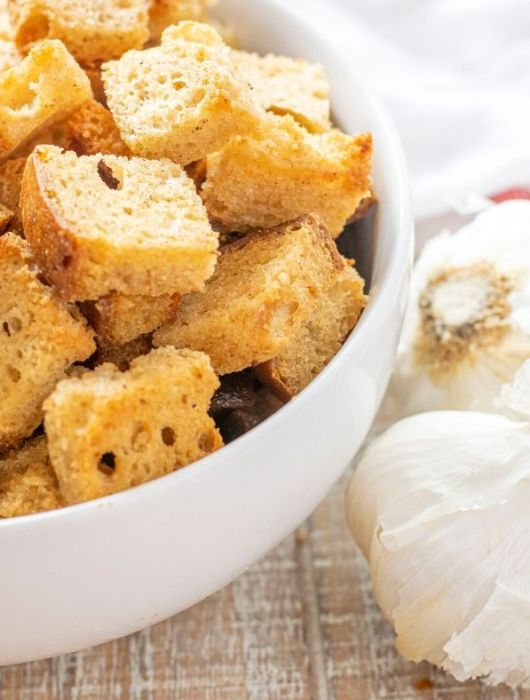 bowl of garlic butter croutons with bulbs of garlic