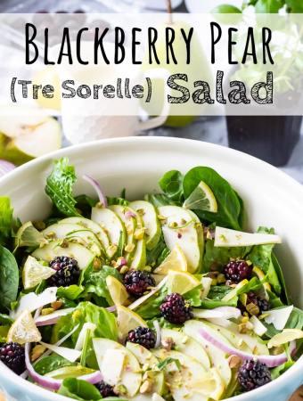 Romaine Lettuce, spinach, blackberries, parmesan, purpole onions, basil, and lemon vinaigrette in blue bowl.