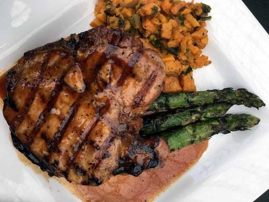 The porterhouse pork chop with bourbon glaze and savory sweet potato hash. | Photo by Steve Coomes