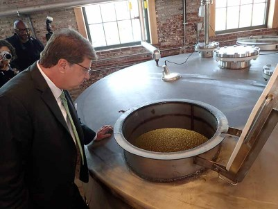 Angel's Envy CIO, Wes Henderson, looks into a mash fermenter. | Photo by Steve Coomes
