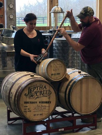 Alicia White and Dave Carpenter thieve samples of Bloody Butcher Bourbon from different-size barrels to let guests compare. | Photo by Steve Coomes