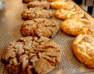 Ginger molasses cookies with other tempting baked goodies sharing the rack.