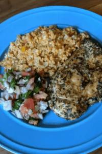 Chicken on a blue plate with caulirice and bruschetta