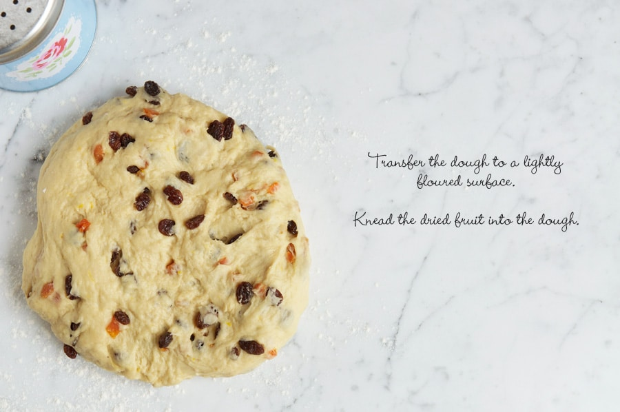 Step by step photos for making fruit loaf. Bread dough on marble work surface with dried fruit added.