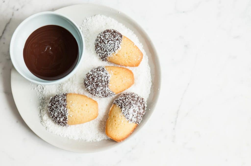 lamington madeleines in bowl of coconut with small bowl of melted chocolate