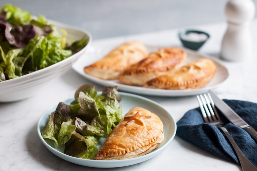 ham and cheese hand pies on blue plate with salad and blue napkin